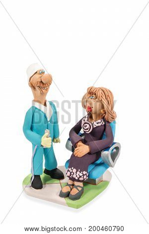 Clay figurine of a standing dentist and patient sitting in a chair isolated on a white background