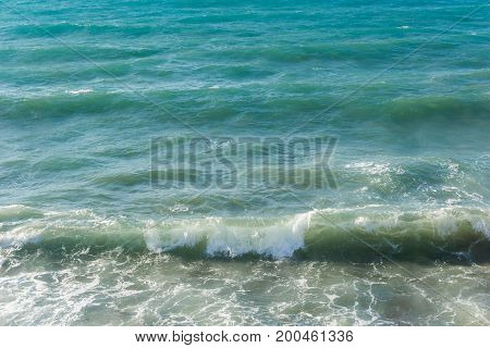 View on beautiful turquoise Waves of an tropical Ocean on a sunny Day. Clsoe-up of a turquoise Sea. Natural Background