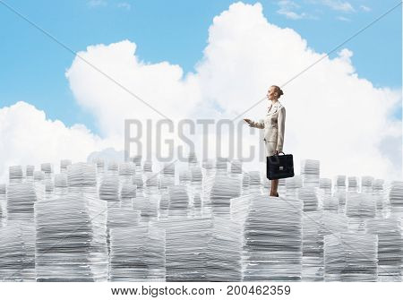 Confident business woman in suit standing on pile of documents with cloudly skyscape on background. Mixed media.