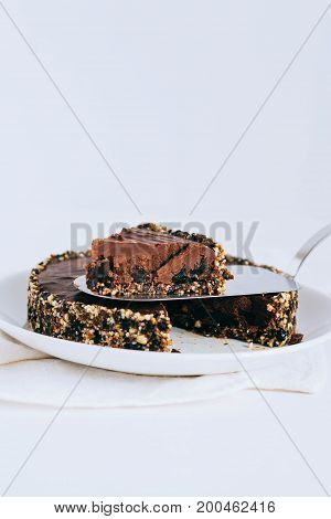 Useful chocolate raw tart with nuts a piece of tart.