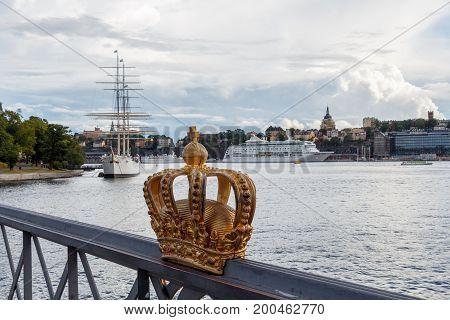 Golden crown on Skeppsholm bridge with Stockholms slot (royal palace) in the background - Stockholm - Sweden - Scandinavia - Europe