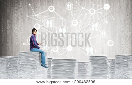 Young man in casual wear sitting on pile of documents with social network structure on background. Mixed media.