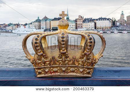 Golden Crown On Skeppsholm Bridge With Stockholms Slot (royal Palace) In The Background - Stockholm