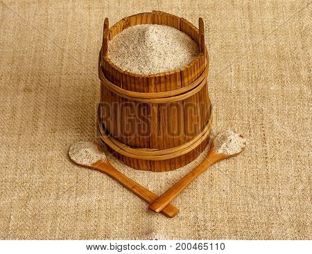Buckwheat flour in wooden canister with two wooden spoons on sackcloth