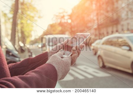 Girl holding cellphone in urban surroundings and crossing the street - danger!