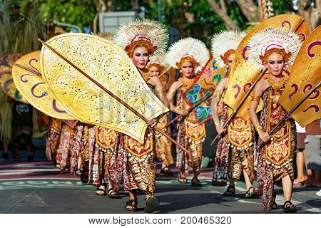 DENPASAR BALI ISLAND INDONESIA - JUNE 11 2016: Group of Balinese people. Beautiful dancer women in traditional costumes dance on street parade at art and culture festival.