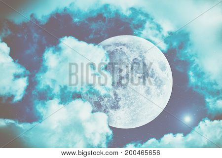 Full Moon behind the clouds on a night sky.