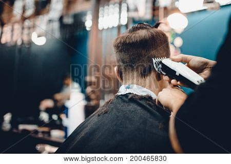 Male hippy customer in barbershop hairdresser on fashionable haircut, rear view. They cut her hair, put her hair dryer and wax. Concept of hair care. Toned photo.