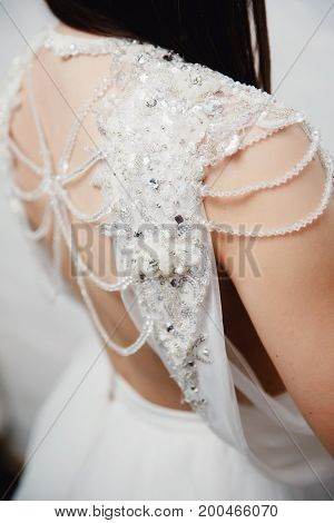 Close-up decoration for a wedding dress with strings, rhinestones, diamonds, shines and beads. Back view.