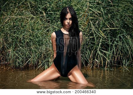 A Sexy Woman Or Girl, In A Seductive Body Suit, Sits Sexually In The Water, Spreading Her Legs Wide