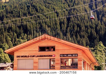 Wengen Bernese Oberland Switzerland - JULY 31 2017 : Wengen Mannlichen Aerial Cableway over wooden chalet with announcement for the 2018 Lauberhorn Ski World Cup