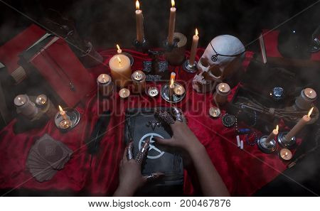 Witchcraft composition with witch's hands, satanic magic book, skull, candles, tarot cards, crystal and amulets. Halloween and occult concept, black magic ritual.