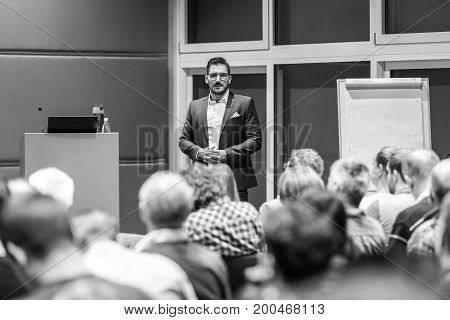 Speaker giving a talk at conference meeting business event. Audience at the conference hall. Business and Entrepreneurship concept. Black and white image.