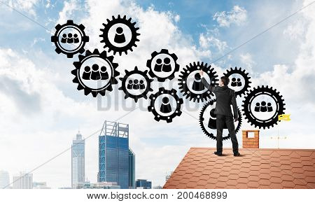 Young man standing with back on roof and drawing gear teamwork concept. Mixed media