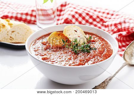 gazpacho in white bowl with bread and thyme garnish