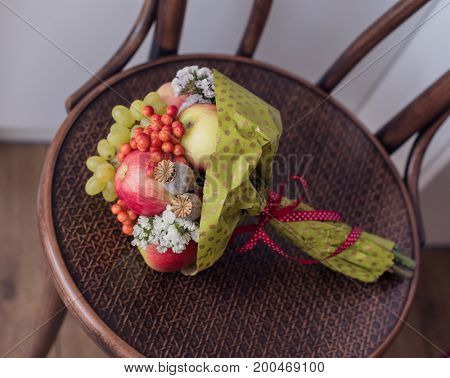 Bouquet of fruits on wooden chair.