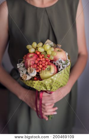 Bouquet of fruits in the girl hands.