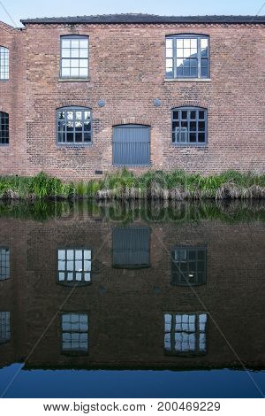 windows and door on the side of an old, industrial, red brick building alongside the Birmingham canal, reflected in calm water