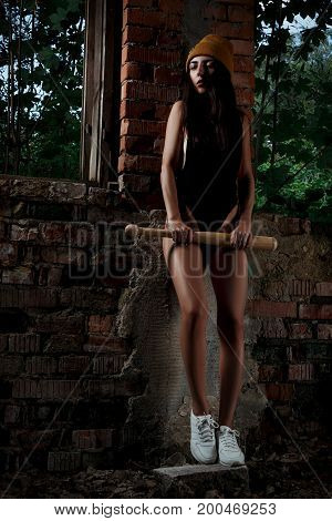 A Girl In A Hat And A Body Suit With A Bat Is Standing In An Abandoned Building With Brick Walls