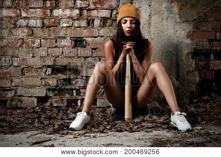A Girl In A Hat And A Bodicuit With A Bat Sits In An Abandoned Building With Brick Walls
