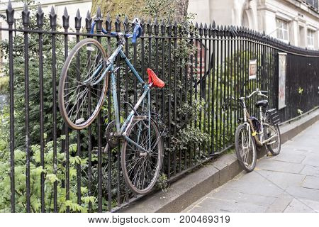 Bicycles chained to railings in London, UK. One bike is completely off the floor