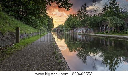 Sunset over the canal in Birmingham, UK, on a deserted footpath, with foliage flanking the tow path. The sun is creating a dramatic red and orange cloudscape in the sky