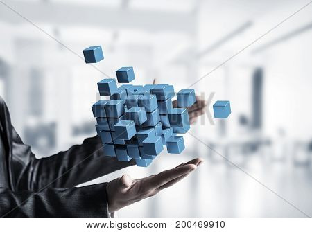 Cropped image of business woman hands holding multiple blue cubes in hands with office view background. Mixed media.