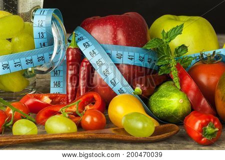 Glasses of water and a tailor's meter. Fruits and vegetables. The concept of weight loss. Healthy diet