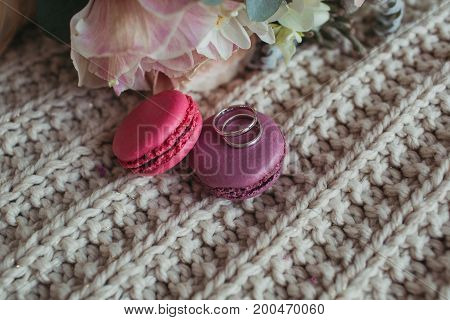 Wedding rings on the colorful macarons with flowers