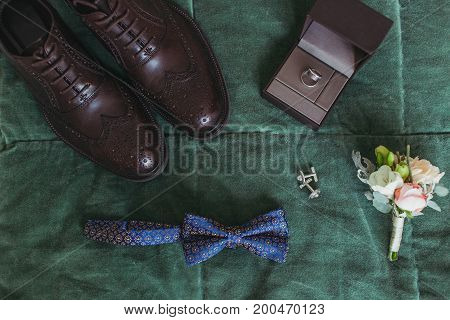 Closeup of elegant stylish dark male accessories on green background. Top view of bow-tie, belt, shoes, floral corsage, golden rings. Preparation for wedding concept. Horizontal photo