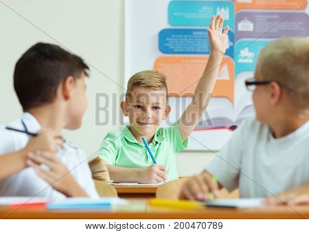 Portrait Of Schoolboy Raises His Hand At The Lesson