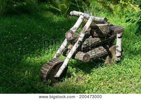 In the forest in the clearing stands a motorcycle from wooden logs. On the seat of the bike is the basket of flowers.