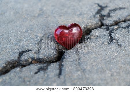 Many cracks on the asphalt. On the big crack lies heart of glass. The symbol of the rupture of relations. A split or crack in love.