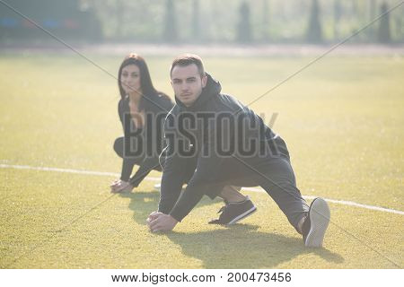 Sports Couple Stretching Body In The Park