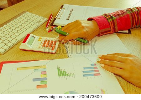 Close-up of a spreadsheet with pen and calculator. view of bookkeeper or financial inspector hands making report calculating or checking balance - Retro color