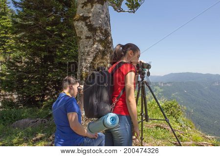 Traveller is looking the nature from the mountain with binoculars tripod and video camera. Eco tourism and healthy lifestyle concept
