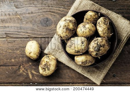Young raw potatoes top view potatoes in a clay plate on a wooden brown table under a plate - a burlap napkin