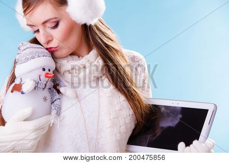 Young woman with computer tablet and little snowman. Girl in white sweater pullover and earmuffs holding pc ebook. Technology and winter fashion.