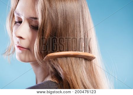 Haircare concept. Female combing brown hair with wooden comb studio shot on blue