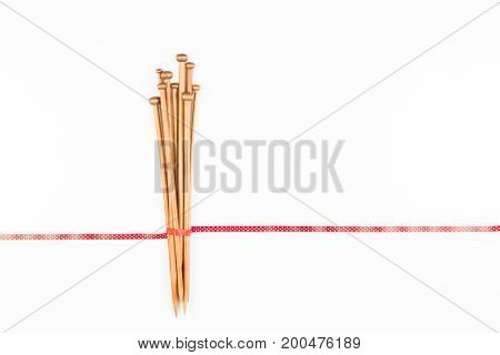 Knitting background. Wooden knitting needles with red and white polka dot ribbon on white background as frame