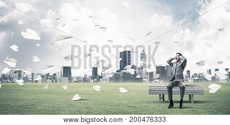 Frustrated businessman sitting on bench and closing ears with hands
