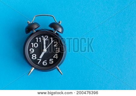Alarm clock with seven o'clock on blue background in minimalistic retro pop art style with place for text. Wake up concept. Back to school. Copy space. Top view.