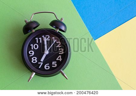 Alarm clock with six o'clock on colorful background in retro pop art style. Wake up concept. Back to school. Top view.