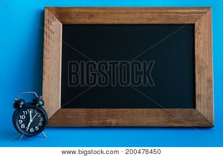 Empty blackboard with place for text with alarm clock on blue background. Alarm clock with seven o'clock in retro pop art style. Wake up concept. Back to school. Copy space.