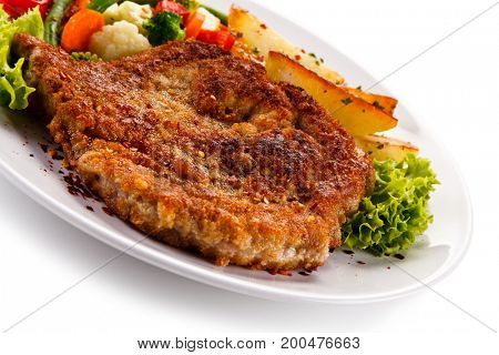 Fried pork chop, baked potatoes and vegetable salad