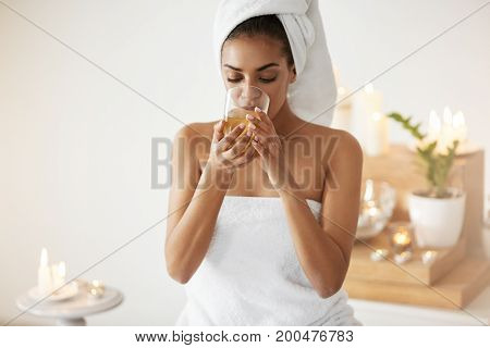 Young tender african girl with towel on head drinking tea resting in spa salon.
