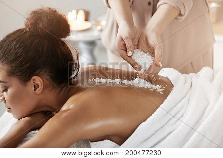 Young beautiful african girl relaxing enjoying spa health massage with sea salt.