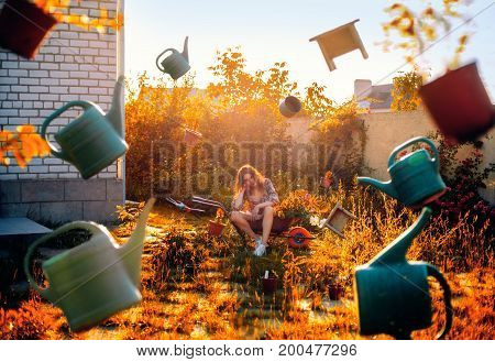 Garden Concept. Young Woman Gardener Sits On Wheelbarrow And Garden Tools Fly Around Her. Perfectly