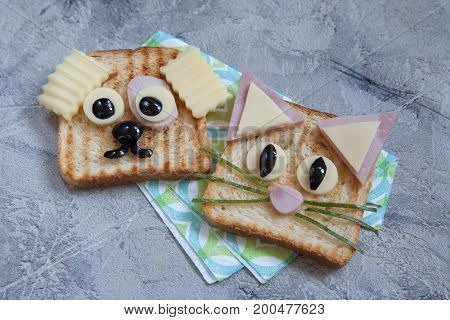 Funny dog and cat sandwich for kids lunch on a table.