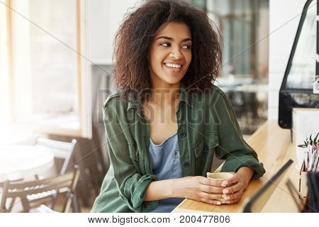 Young beautiful african girl student resting relaxing sitting in cafe smiling drinking coffee. Copy space.